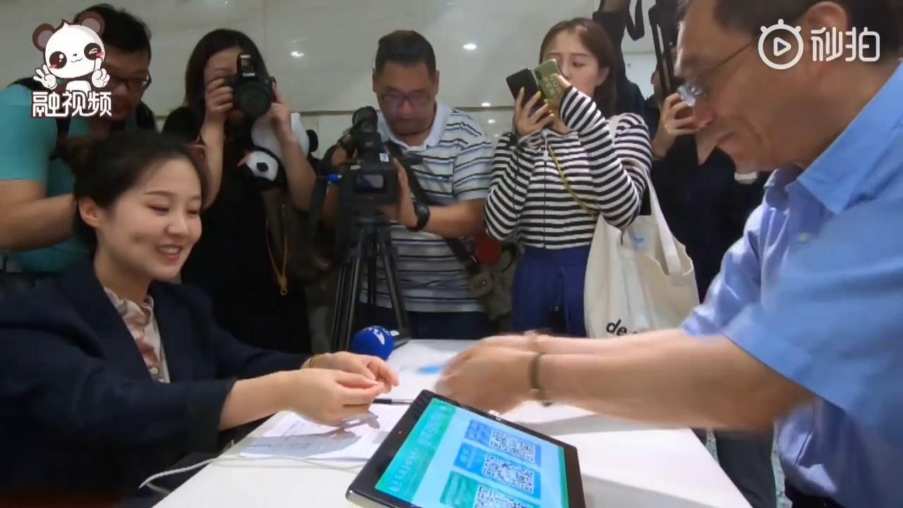 """台胞黄先生在南京市政务服务中心台胞服务窗口办理一卡通。台胞服务窗口是南京市台办在贯彻落实""""31条措施""""过程中专门为台胞开设的,为在地台胞提供了很都多生活和工作上的便利。图片"""